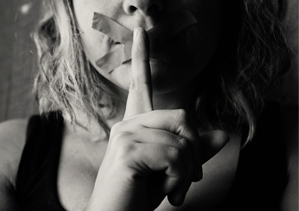 Woman holding finger to lips, mouth has tape across it